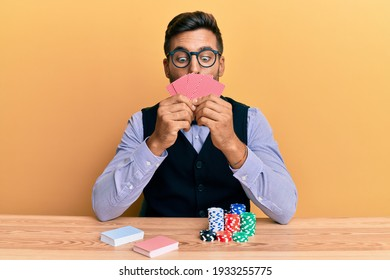 Handsome hispanic croupier man sitting on the table with poker chips and cards making fish face with mouth and squinting eyes, crazy and comical.