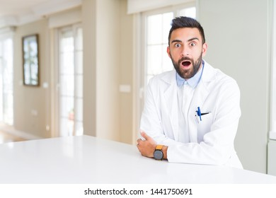 Handsome hispanic doctor or therapist man wearing medical coat at the clinic afraid and shocked with surprise expression, fear and excited face.