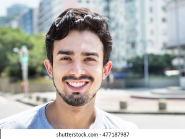 Handsome hispanic guy in a grey shirt in city