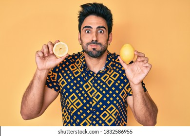 Handsome hispanic man with beard holding lemon puffing cheeks with funny face. mouth inflated with air, catching air.