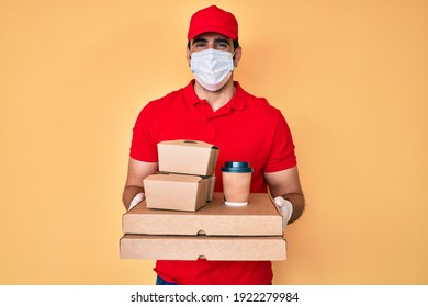 Handsome hispanic man with beard holding delivery food wearing medical mask smiling with a happy and cool smile on face. showing teeth.