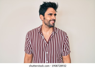 Handsome hispanic man with beard wearing casual clothes looking away to side with smile on face, natural expression. laughing confident.