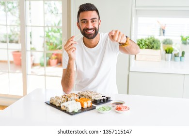Handsome hispanic man eating asian sushi using chopsticks pointing with finger to the camera and to you, hand sign, positive and confident gesture from the front