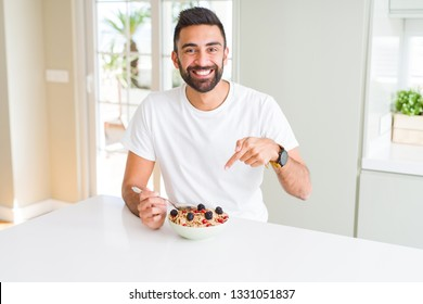 Handsome hispanic man eating healthy breakfast in the morning at home very happy pointing with hand and finger