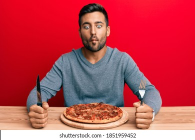 Handsome hispanic man eating tasty pepperoni pizza making fish face with mouth and squinting eyes, crazy and comical.