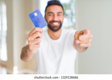 Handsome hispanic man holding credit card pointing with finger to the camera and to you, hand sign, positive and confident gesture from the front