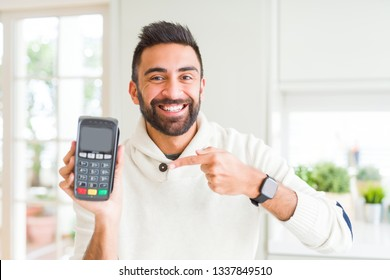 Handsome hispanic man holding point of sale terminal dataphone very happy pointing with hand and finger