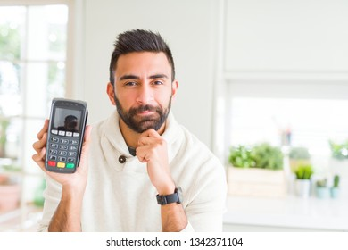 Handsome hispanic man holding point of sale terminal dataphone serious face thinking about question, very confused idea