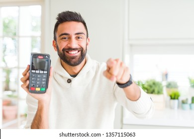 Handsome hispanic man holding point of sale terminal dataphone pointing with finger to the camera and to you, hand sign, positive and confident gesture from the front