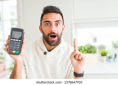 Handsome hispanic man holding point of sale terminal dataphone surprised with an idea or question pointing finger with happy face, number one