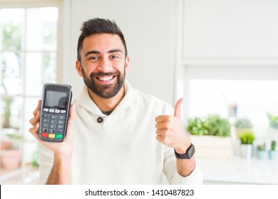Handsome hispanic man holding point of sale terminal dataphone happy with big smile doing ok sign, thumb up with fingers, excellent sign