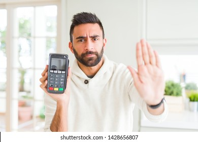Handsome hispanic man holding point of sale terminal dataphone with open hand doing stop sign with serious and confident expression, defense gesture
