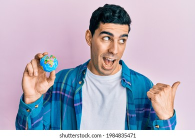 Handsome hispanic man holding small world ball pointing thumb up to the side smiling happy with open mouth