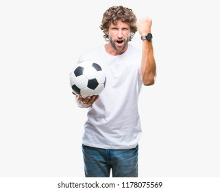Handsome hispanic man model holding soccer football ball over isolated background annoyed and frustrated shouting with anger, crazy and yelling with raised hand, anger concept
