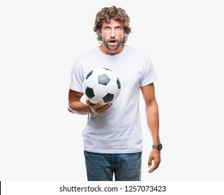 Handsome hispanic man model holding soccer football ball over isolated background scared in shock with a surprise face, afraid and excited with fear expression