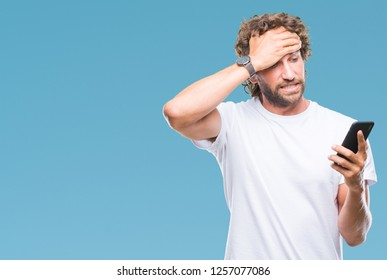 Handsome hispanic man model sending message texting using smartphone over isolated background stressed with hand on head, shocked with shame and surprise face, angry and frustrated. Fear and upset