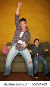 Handsome Hispanic man playing Video game with bored young boy