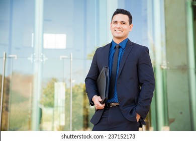 Handsome Hispanic man in a suit carrying his resume and waiting for a job interview and smiling