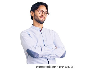 Handsome hispanic man wearing business shirt and glasses looking to the side with arms crossed convinced and confident