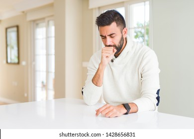 Handsome hispanic man wearing casual white sweater at home feeling unwell and coughing as symptom for cold or bronchitis. Healthcare concept.