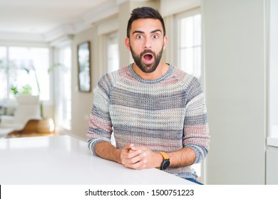 Handsome hispanic man wearing casual sweater at home afraid and shocked with surprise expression, fear and excited face.