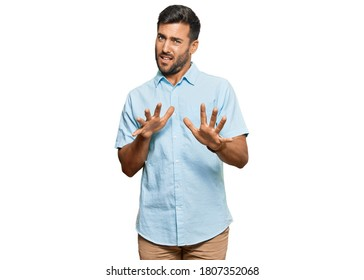Handsome hispanic man wearing casual clothes disgusted expression, displeased and fearful doing disgust face because aversion reaction. with hands raised