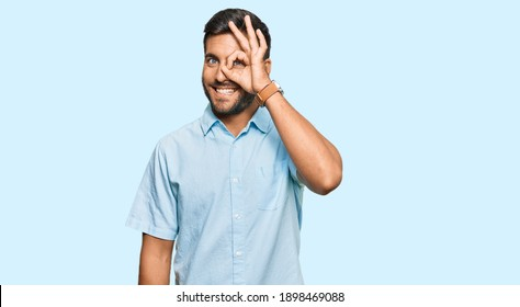 Handsome hispanic man wearing casual clothes doing ok gesture with hand smiling, eye looking through fingers with happy face.