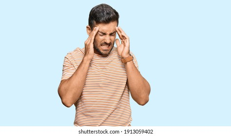 Handsome hispanic man wearing casual clothes with hand on head, headache because stress. suffering migraine.