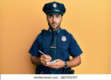 Handsome hispanic man wearing police uniform writing traffic fine relaxed with serious expression on face. simple and natural looking at the camera.