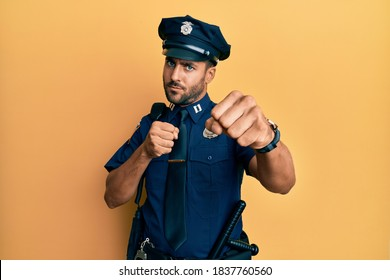 Handsome hispanic man wearing police uniform punching fist to fight, aggressive and angry attack, threat and violence
