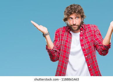 Handsome hispanic model man over isolated background clueless and confused expression with arms and hands raised. Doubt concept.