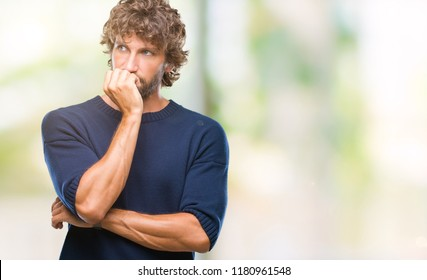 Handsome hispanic model man wearing winter sweater over isolated background looking stressed and nervous with hands on mouth biting nails. Anxiety problem.