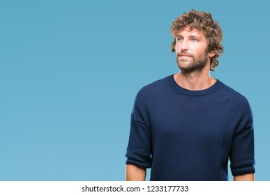 Handsome hispanic model man wearing winter sweater over isolated background looking away to side with smile on face, natural expression. Laughing confident.