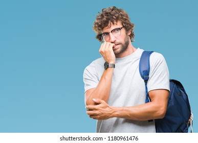 Handsome hispanic student man wearing backpack and glasses over isolated background looking stressed and nervous with hands on mouth biting nails. Anxiety problem.