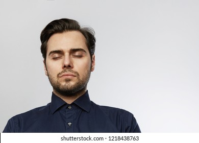 Handsome hispanic trendy man posing with closed eyes isolated on a white empty background.