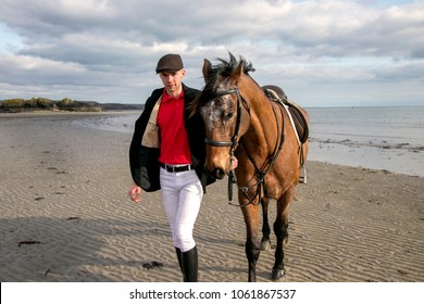 Handsome horse rider in traditional outfit of white trousers, black boots and red polo shirt with his horse on Cornish beach