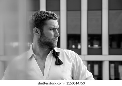 Handsome hunky male with loose bowtie and unbuttoned shirt stands on hotel balcony with skyscraper as backdrop
