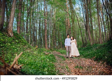 handsome husband and his pregnant wife are walking in the forest