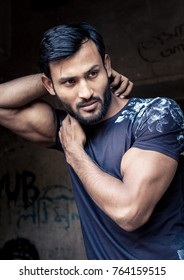 Handsome indian and arab looking male model with big biceps and black hair and a trendy beard, posing in a navy blue fashion tshirt