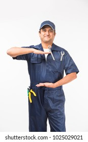 Handsome Indian Auto Mechanic presenting something or showing empty biz card while holding tools like spanner in one hand