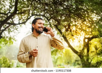 Handsome indian bearded man talking on phone in a park