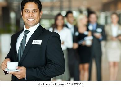 handsome indian businessman having coffee break during seminar