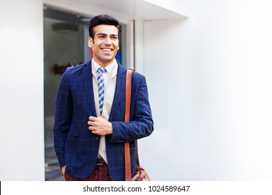 Handsome Indian businessman looking forward near office building