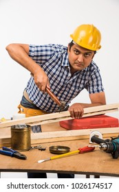 Handsome Indian Carpenter or wood worker in action, isolated over white background