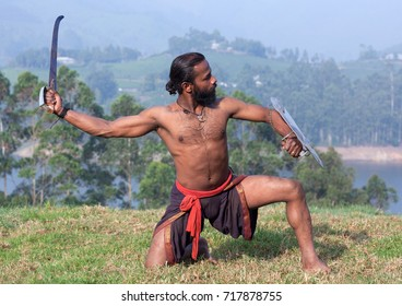 Handsome Indian fighter with sword and shield performing Kalaripayattu marital art demonstration in Kerala, South India