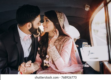 Handsome Indian groom dressed in traditional black suit and pretty bride in pink wedding dress with golden embroidery sit inside the car