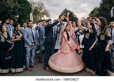 Handsome Indian groom dressed in traditional black suit and pretty bride in pink wedding dress with golden embroidery dance before a car together with their cheerful groomsman and bridesmaids