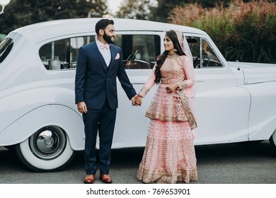 Handsome Indian groom dressed in traditional black suit and pretty bride in pink wedding dress with golden embroidery sit stand before the car
