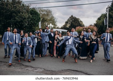 Handsome Indian groom dressed in traditional black suit and pretty bride in pink wedding dress with golden embroidery sit stand before the car together with happy groomsmen in grey suits