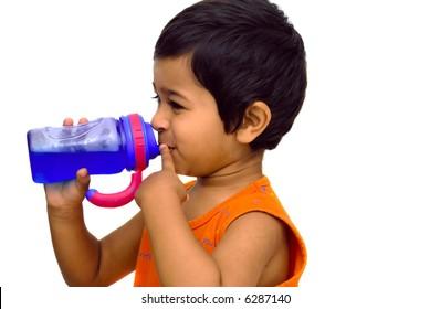 An handsome indian kid having fun drinking juice